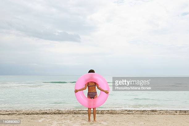 Girl holding inflatable ring on beach, rear view