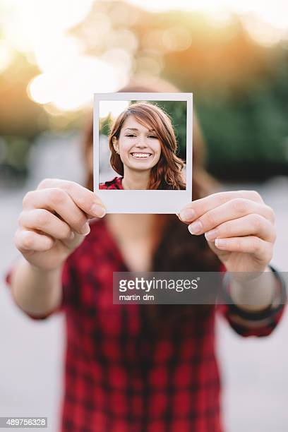 Girl holding instant photo
