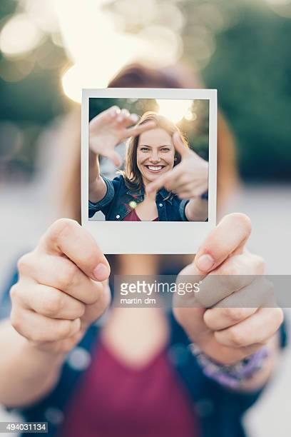 Jeune fille tenant un polaroid selfie