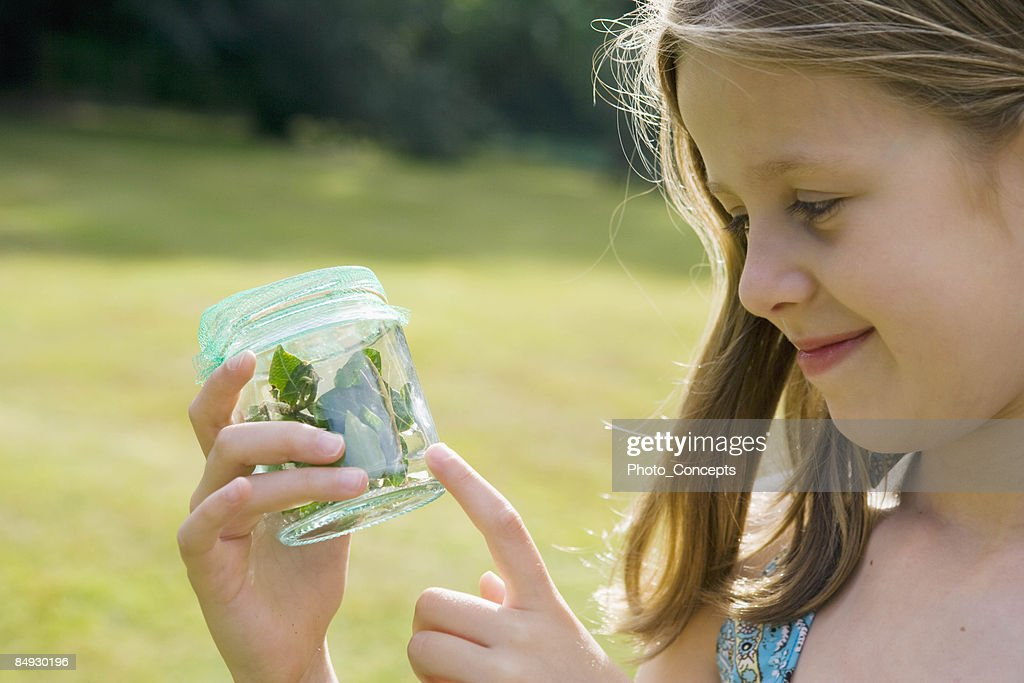Girl holding jar of insects : Stock Photo