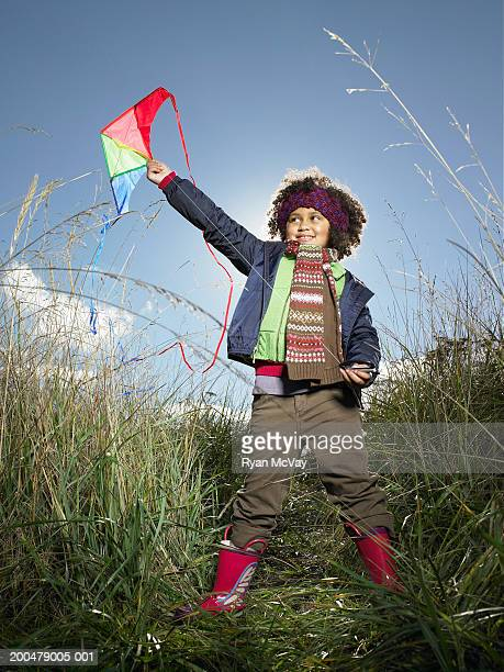 Girl (5-7) holding kite above head in tall grass, smiling