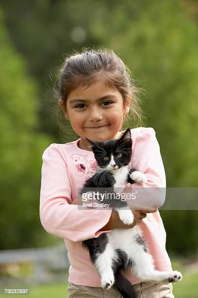 Girl (6-7) holding kitten outdoors, portrait