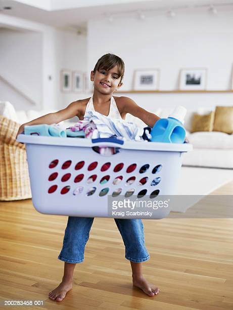 Girl (6-8) holding large basket of laundry, smiling, portrait