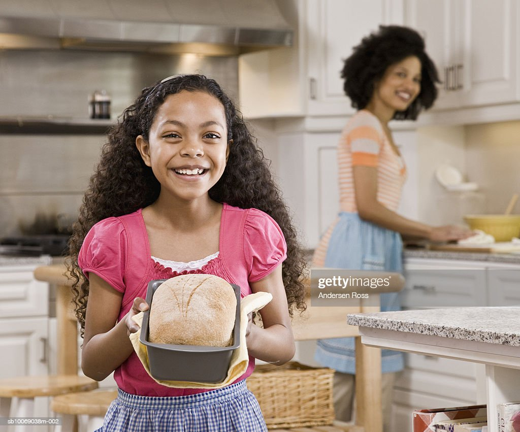 Girl (10-11) holding loaf of freshly baked bread, mother smiling in background : Stock Photo