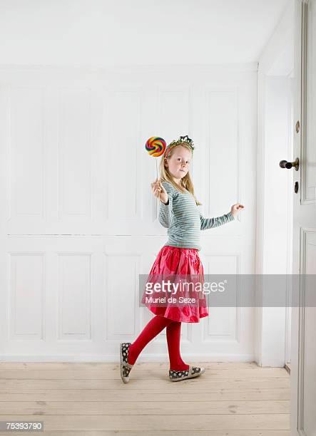 Girl (8-9) holding lollipop, portrait