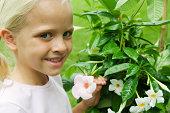 Girl holding mandevilla blossom, smiling, portrait