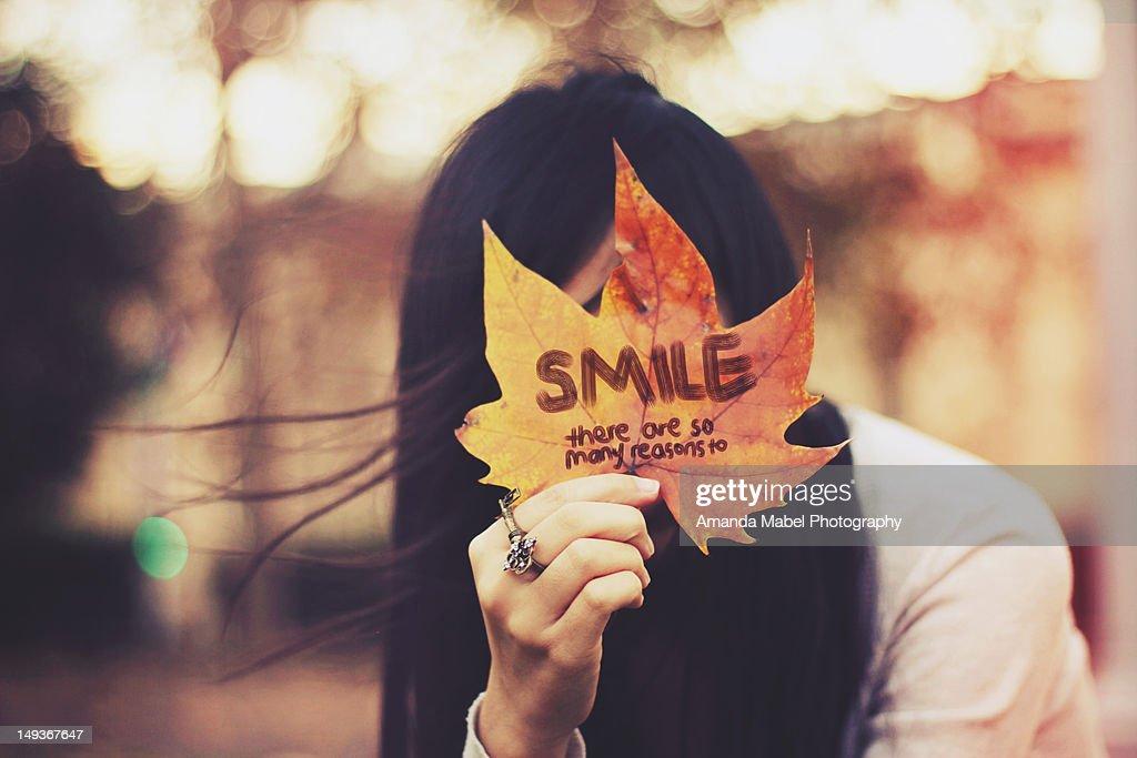 Girl holding maple leaf : Stock Photo