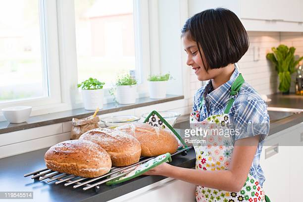 Girl holding metal grate with hot bread loafs