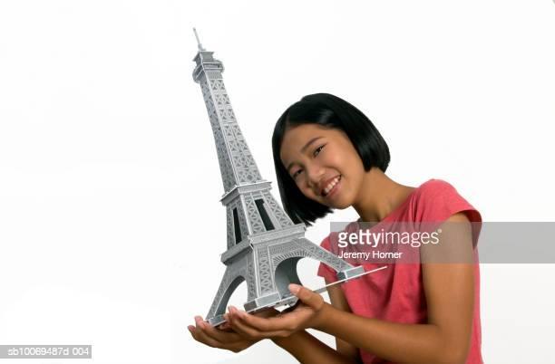 Girl (10-11) holding model of Eiffel Tower