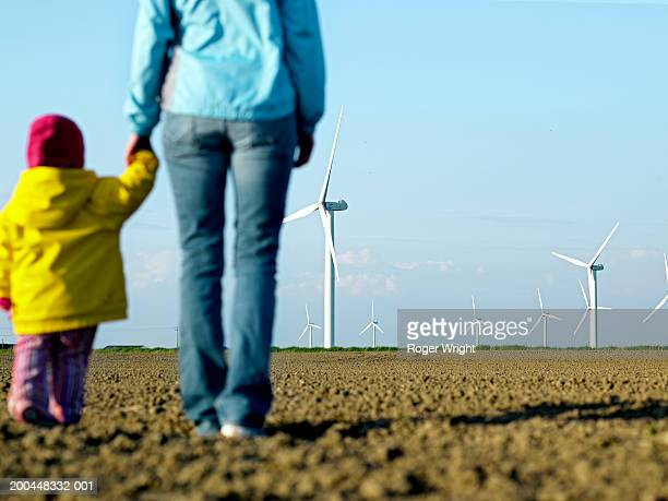 Girl (2-4) holding mother's hand, looking at wind farm, rear view