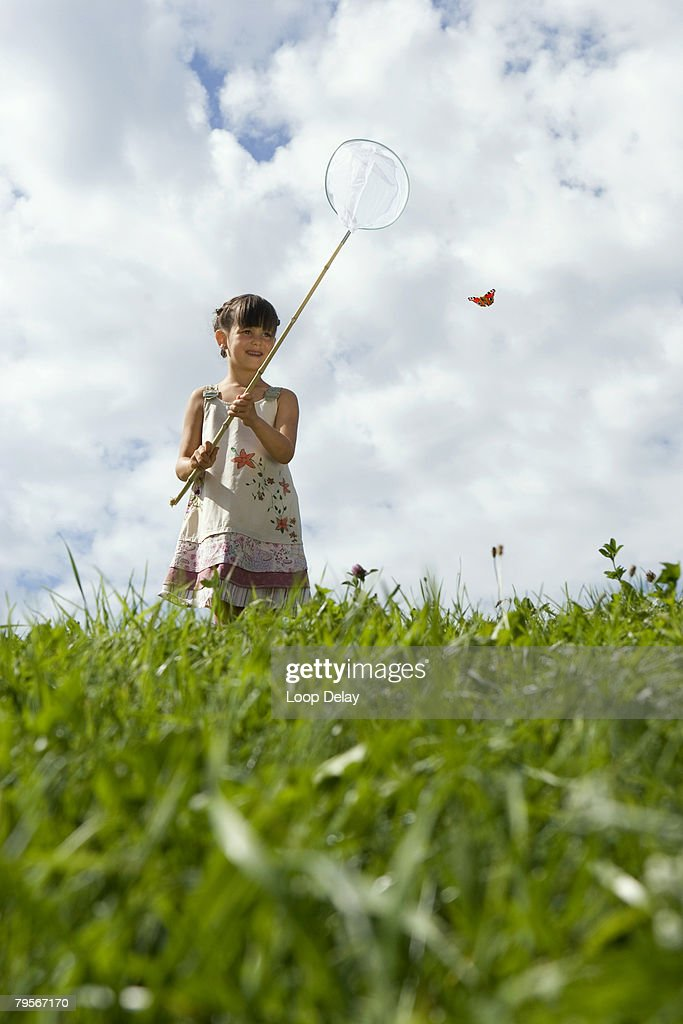 'Girl (7-9) holding net, trying to catch butterfly'