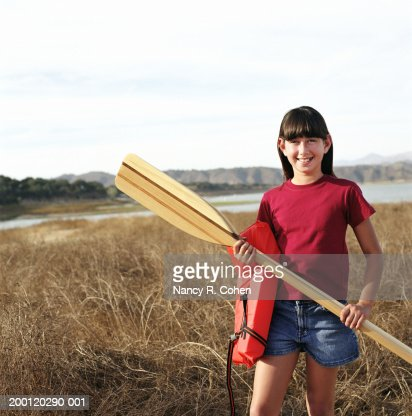 Girl (8-10) holding oar and life jacket, smiling, portrait : Stock Photo