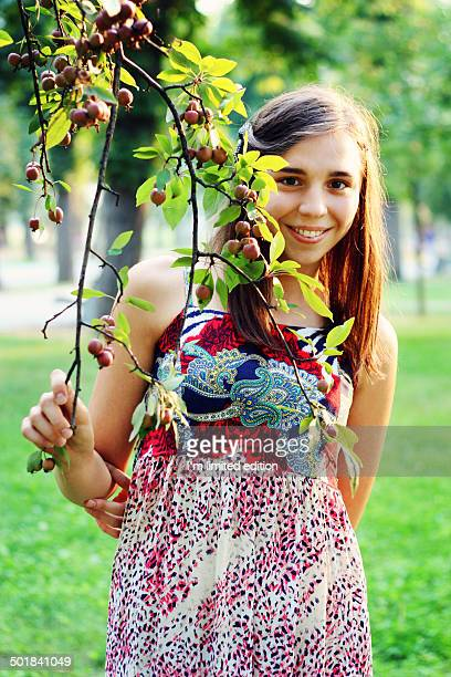 Girl holding on a wild apple tree branch