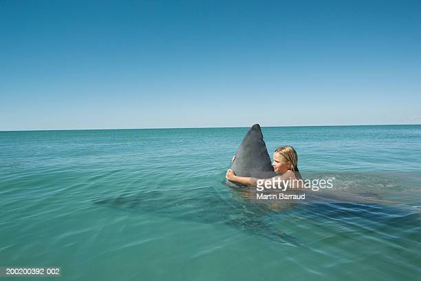 Girl (8-10) holding onto fin of Great white shark in sea