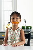 Girl (3-5) holding orange rind in mouth, portrait