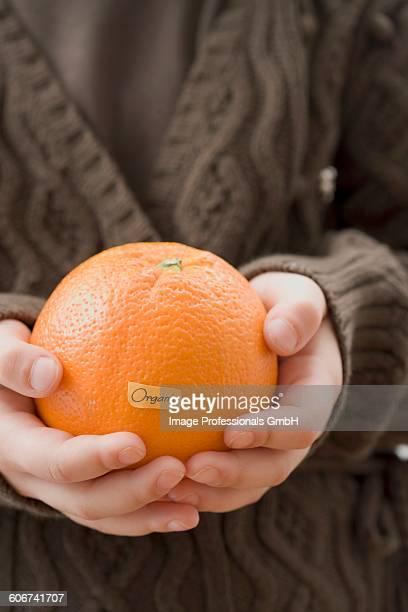 Girl holding organic orange