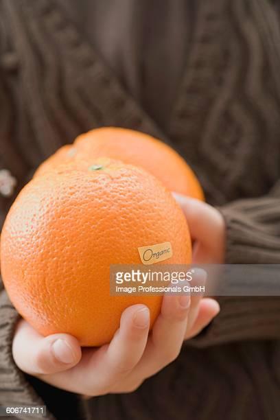 Girl holding organic oranges