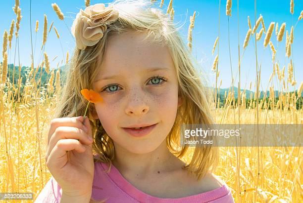 Girl holding ornage poppy flower in field
