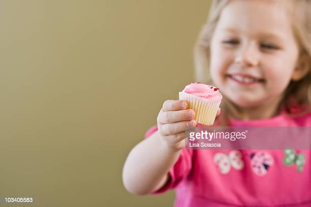 A girl holding out a cupcake, focus on hand
