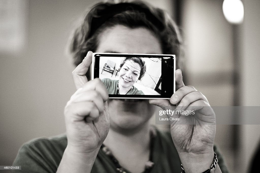 Girl Holding Phone Up With Her Picture On It : Stock Photo