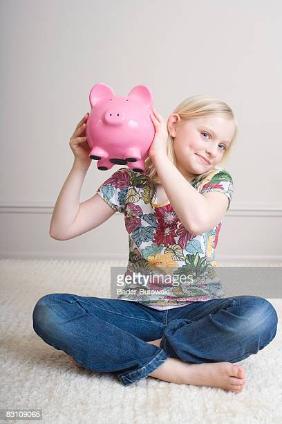 Girl (8-9) sitting with holding piggybank, portrait