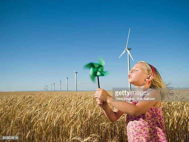 Girl holding pinwheel on wind farm