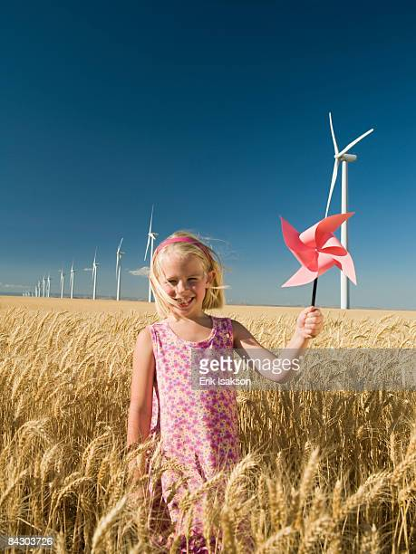 Girl holding pinwheel on wind farm