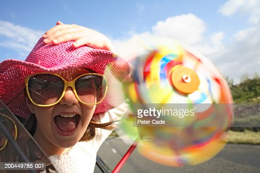 Girl (9-11) holding pinwheel, sticking head out car (blurred motion) : Stock Photo