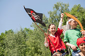 Girl holding pirate flag with her friends in adventure playground, Bavaria, Germany