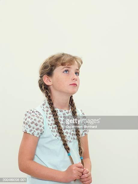 Girl (9-11) holding plaited hair, looking upwards