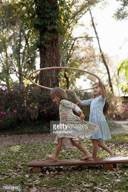 Girl holding plastic hoop above her sisters head