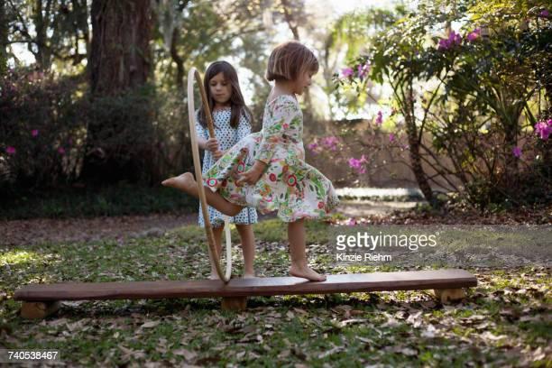 Girl holding plastic hoop, sister running through