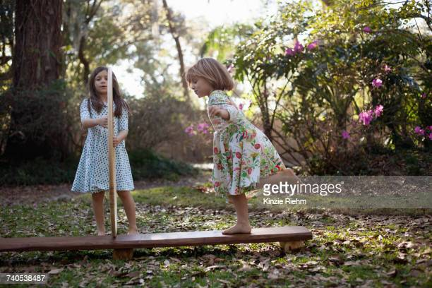 Girl holding plastic hoops with sister running through