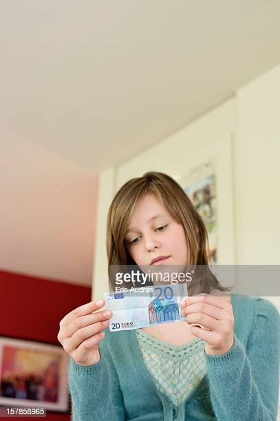 Girl holding pocket money at home