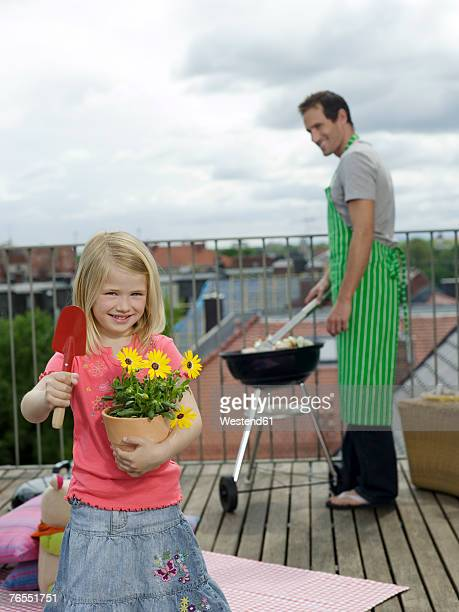Girl (6-7) holding pot plant and shovel, father in background