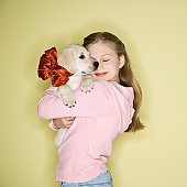 Girl (10-11) holding puppy dog wearing bow