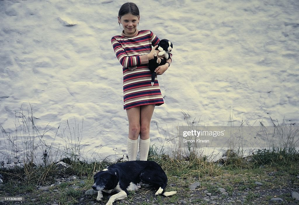 Girl holding puppy with dog at farm