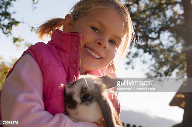 'Girl holding rabbit, portrait'