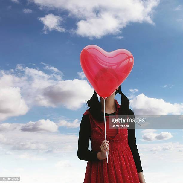 Girl holding red heart shape balloon