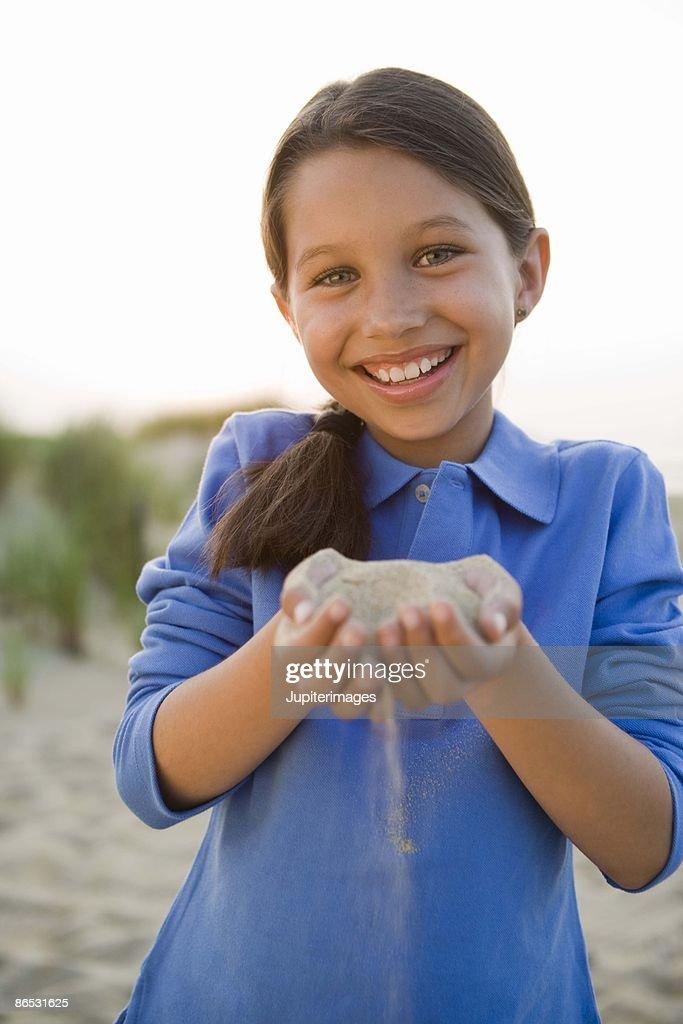 Girl holding sand : Stock Photo
