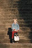 Girl (4-5) holding satchel, outdoors