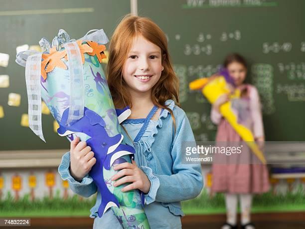 Girl (6-7) holding school cone, smiling, portrait