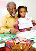 Girl holding schoolwork with grandfather