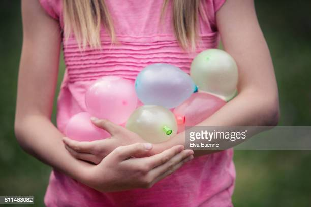 Girl holding several pastel coloured water balloons