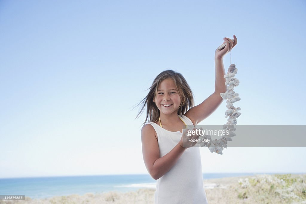 Girl holding shell necklace on beach : Stock Photo