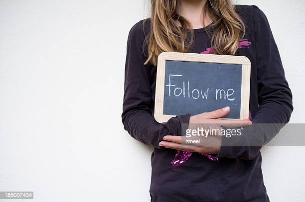 Girl holding sign with Follow me