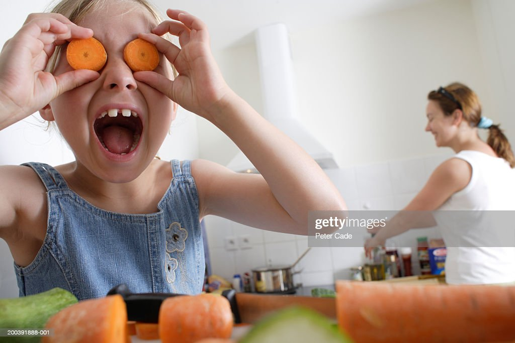 Girl (7-9) holding sliced carrots in front of eyes, mother in : Stock Photo