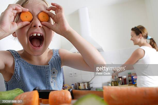 Girl (7-9) holding sliced carrots in front of eyes, mother in