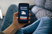 Girl holding smart phone with delivery tracking concept on screen. All screen content is designed by me