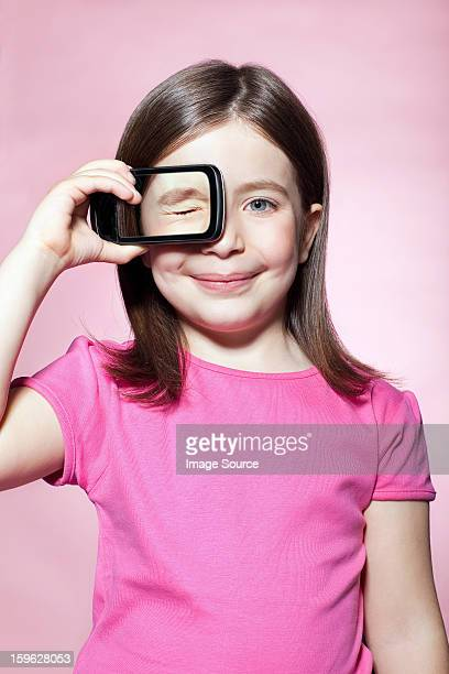 Girl holding smartphone over eye